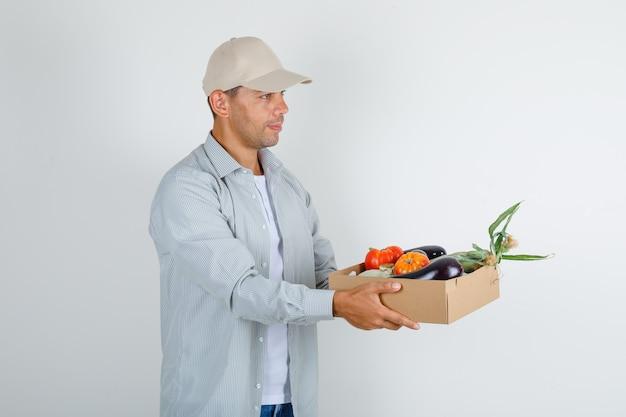 Молодой человек держит коробку с овощами в рубашке и кепке