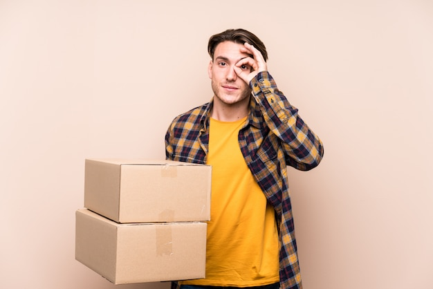 Young man holding boxes excited keeping ok gesture on eye