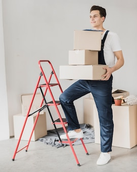 Young man holding boxes with foot on ladder