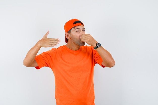Young man holding breath with fingers on nose in orange t-shirt and cap and looking disgusted