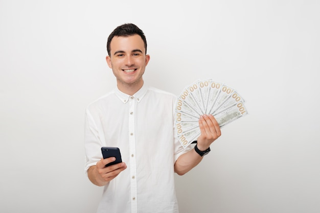 Young man holding a bunch of dollars and his smart phone. mobile banking. online betting.