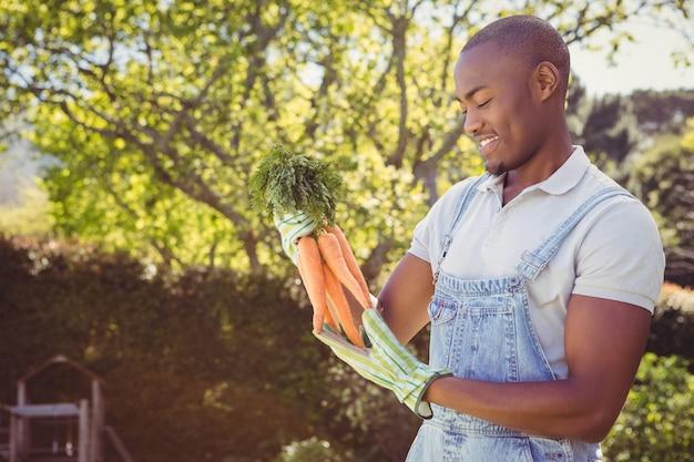 Молодой человек держит пучок моркови