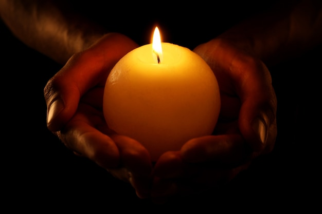 Young man holding burning candle in darkness