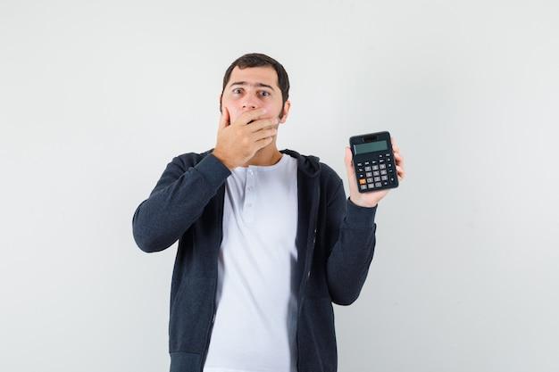 Молодой человек держит калькулятор и прикрывает рот рукой в белой футболке и черной толстовке с капюшоном на молнии и выглядит оптимистично, вид спереди.