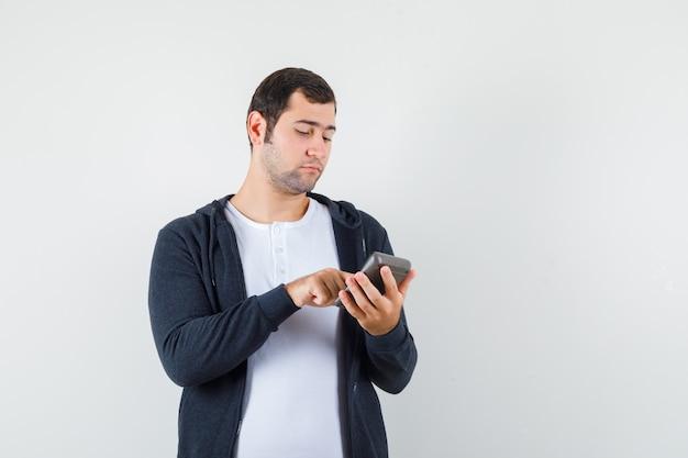 電卓を持って、白いtシャツとジップフロントの黒いパーカーでいくつかの操作を行って、焦点を合わせた正面図を探している若い男。