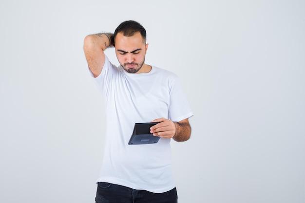 젊은 남자가 계산기를 들고 흰색 티셔츠와 검은 색 바지에 머리 뒤에 손을 잡고 심각한 찾고