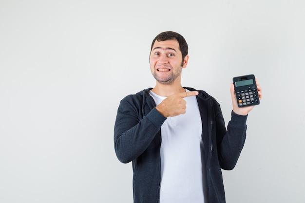 電卓を持って、白いtシャツとジップフロントの黒いパーカーで人差し指を指さし、楽観的に見える若い男。正面図。