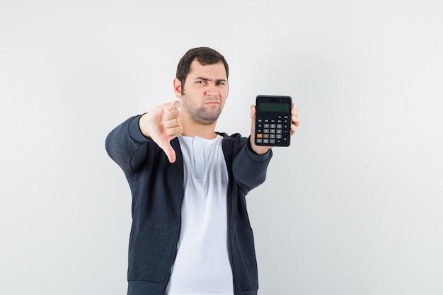 電卓を持って、白いtシャツとジップフロントの黒いパーカーで親指を下に見せて、不機嫌そうな正面図を見て若い男。
