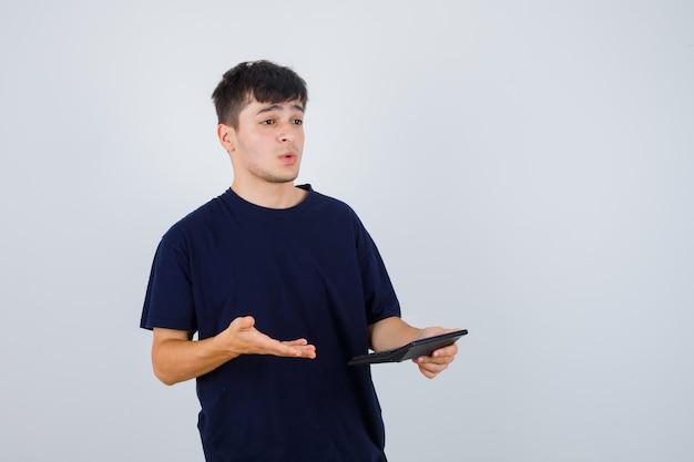 Calcolatrice della holding del giovane in maglietta nera e guardando perplesso, vista frontale