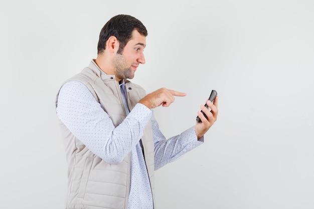 한 손에 계산기를 들고 베이지 색 재킷과 모자에 검지 손가락으로 가리키는 젊은 남자. 전면보기.