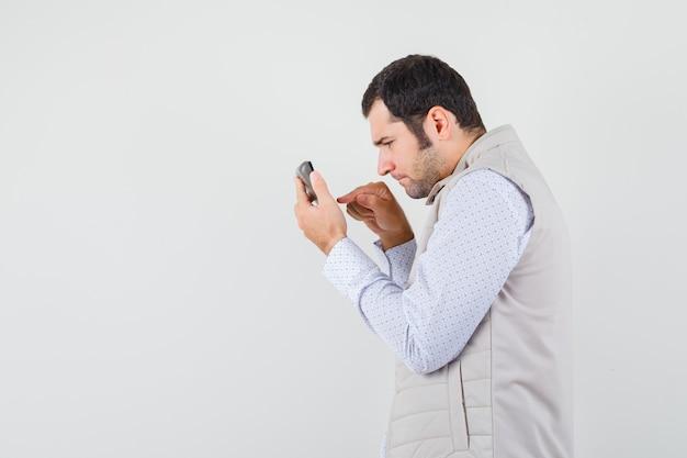 片手に電卓を持って、ベージュのジャケットとキャップで計算しようとし、焦点を当てているように見える若い男。正面図。