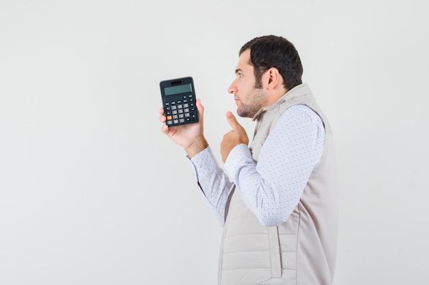 베이지 색 재킷과 모자에 엄지 손가락을 표시하고 잠겨있는 찾고있는 동안 한 손에 계산기를 들고 젊은 남자. 전면보기.