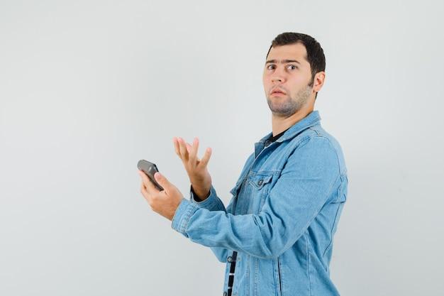 Tシャツ、ジャケットで電卓を持って困惑している若い男。