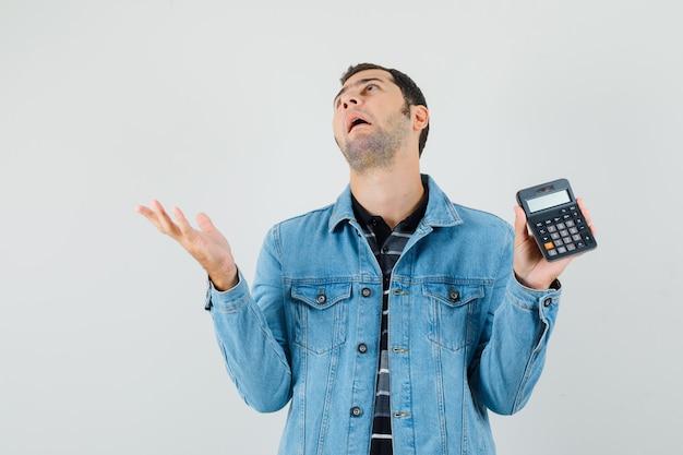 電卓を持って、tシャツ、ジャケットで見上げて、混乱している若い男