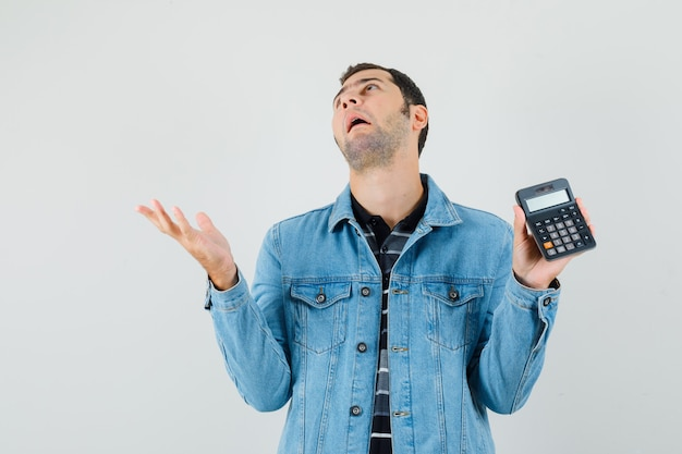 Young man holding calculator, looking up in t-shirt, jacket and looking confused