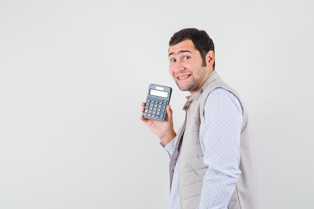 Giovane che tiene la calcolatrice in una mano in giacca e berretto beige e sembra ottimista, vista frontale.