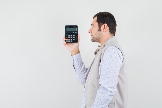 Giovane che tiene la calcolatrice in una mano in giacca e berretto beige e sembra seria, vista frontale.