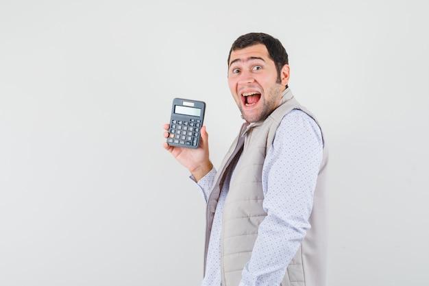 Giovane che tiene la calcolatrice in una mano in giacca e berretto beige e sembra sorpreso, vista frontale.