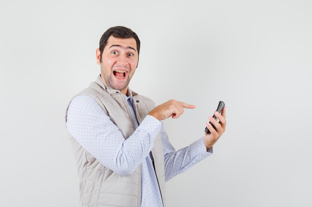 Giovane che tiene la calcolatrice in una mano e punta ad essa con il dito indice in giacca e berretto beige e sembra felice. vista frontale.