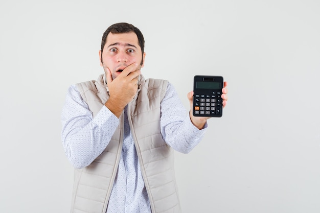 Young man holding calculator in one hand while covering mouth with hand in beige jacket and cap and looking surprised. front view.