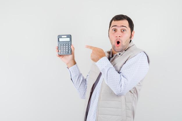 Giovane che tiene la calcolatrice in una mano mentre indica con il dito indice in giacca e berretto beige e sembra sorpreso. vista frontale.