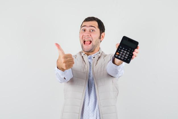 Giovane che tiene la calcolatrice in una mano mentre mostra il pollice in su in giacca e berretto beige e sembra ottimista. vista frontale.
