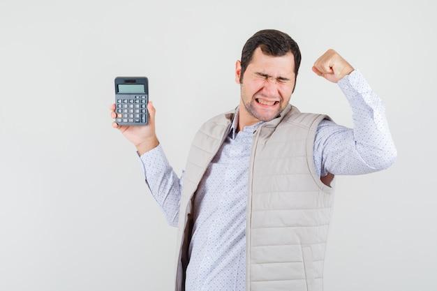 Giovane che tiene la calcolatrice in una mano mentre mostra la posa del vincitore in giacca e berretto beige e sembra eccitata. vista frontale.