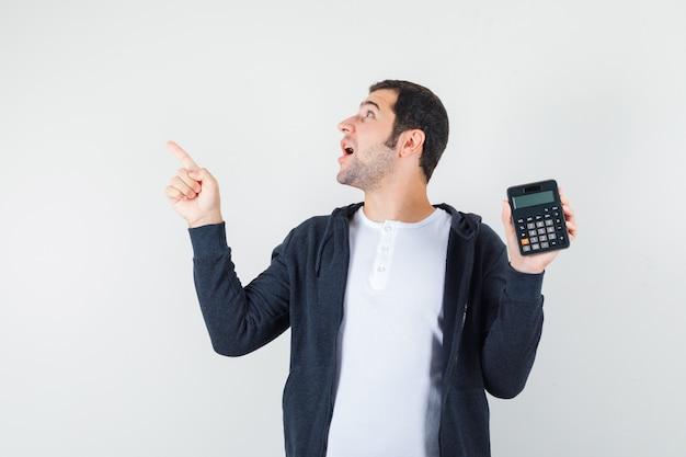 Giovane che tiene la calcolatrice e punta il dito indice a sinistra in maglietta bianca e felpa con cappuccio nera con cerniera e sembra eccitato. vista frontale.
