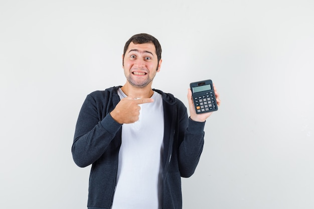 Young man holding calculator and pointing to it in white t-shirt and zip-front black hoodie and looking optimistic , front view.