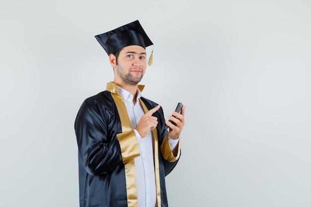 Молодой человек держит калькулятор, указывая вверх в униформе выпускника и выглядит уверенно. передний план.