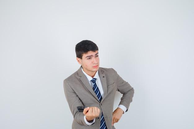 Ragazzo giovane azienda calcolatrice, mettendo la mano sul fianco in abito formale e guardando pensieroso. vista frontale.