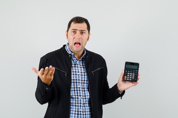 Young man holding calculator in shirt, jacket and looking puzzled