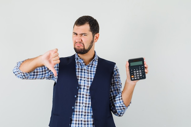 Young man holding calculator, showing thumb down in shirt
