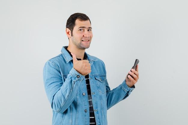 계산기를 들고, t- 셔츠, 재킷에 엄지 손가락을 표시 하 고 유쾌한 찾고 젊은 남자.