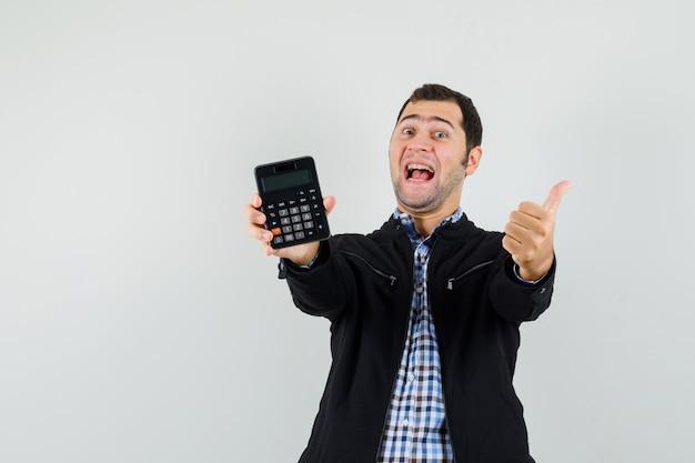 Calcolatrice della holding del giovane, che mostra il pollice in su in camicia, giacca e che sembra felice.