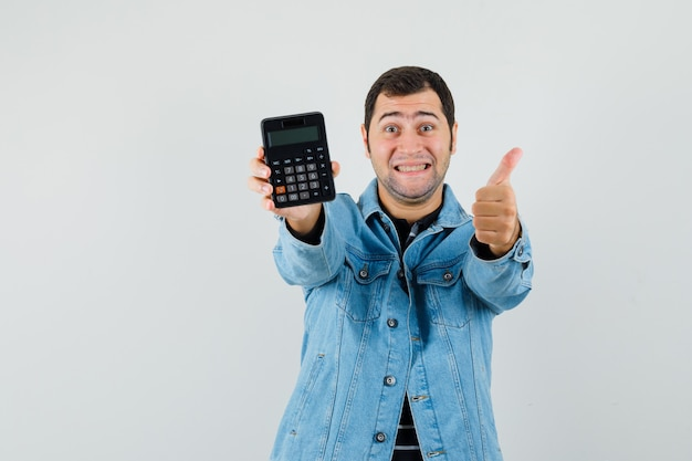 Young man holding calculator, showing thumb up in t-shirt, jacket and looking happy
