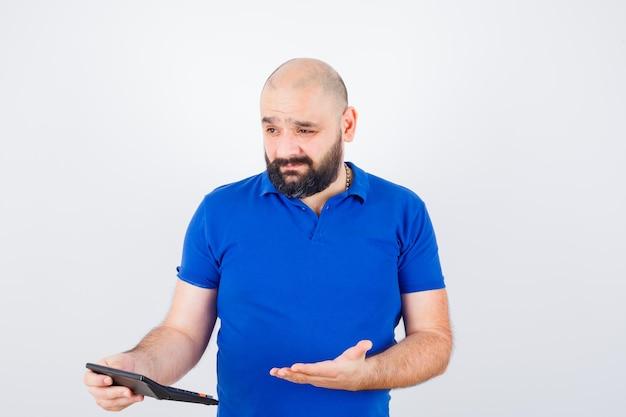 青いシャツで議論し、焦点を当てた、正面図を探している間、電卓を保持している若い男。