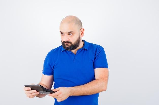 青いシャツを着て目をそらし、集中して見ながら電卓を保持している若い男。正面図。