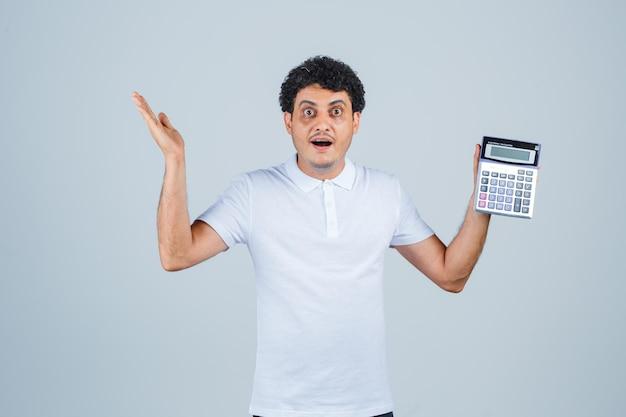 흰색 티셔츠를 입고 손을 들고 놀란 표정으로 계산기를 들고 있는 젊은 남자. 전면보기.