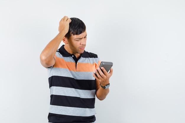 Calcolatrice della holding del giovane mentre si gratta la testa in maglietta e che sembra pensieroso