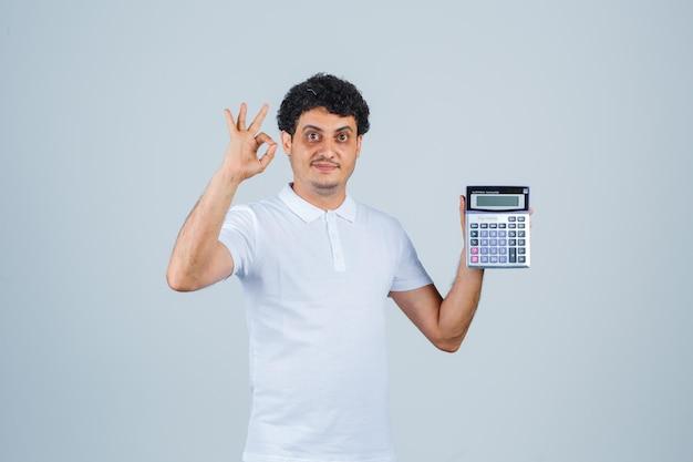 흰색 티셔츠에 확인 제스처를 보여주고 자신감을 보이는 동안 계산기를 들고 있는 젊은 남자. 전면보기.