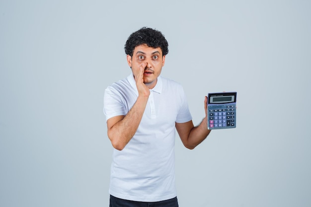 Young man holding calculator while telling secret in white t-shirt and looking excited , front view.