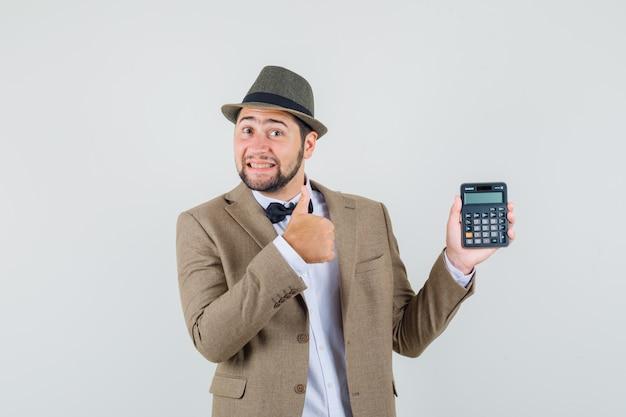 젊은 남자 정장, 모자에 엄지 손가락으로 계산기를 들고 즐거운 찾고. 전면보기.