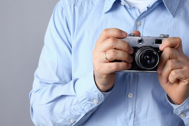 Young man holding a camera, standing on gray background