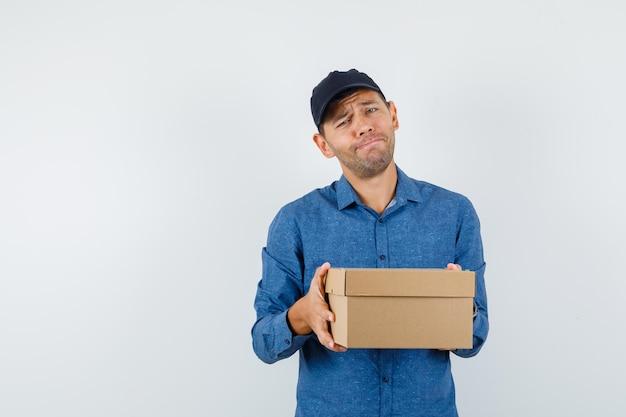 파란색 셔츠, 모자에 마분지 상자를 들고 필사적으로 보이는 젊은 남자.