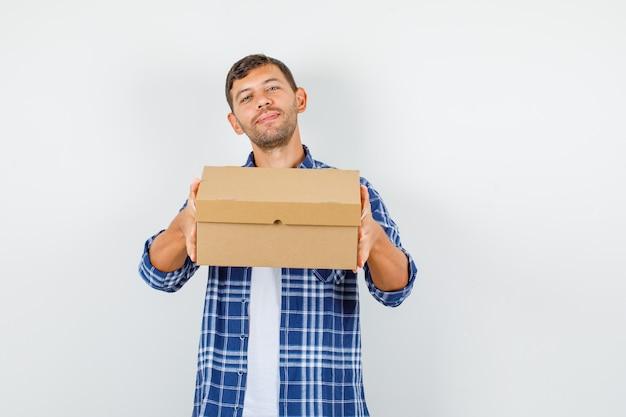 Молодой человек держит картонную коробку в рубашке и выглядит веселым, вид спереди.