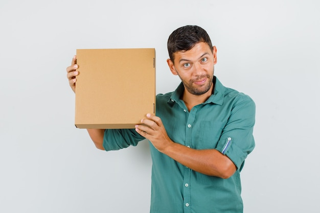 Young man holding cardboard box in shirt and looking curious