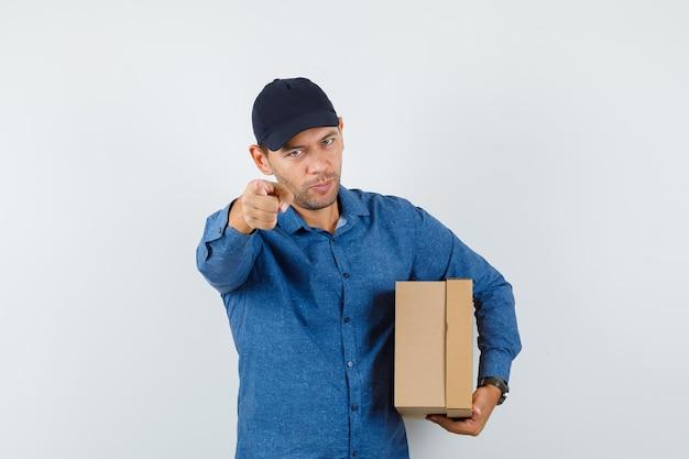 파란색 셔츠, 모자, 전면 뷰에서 카메라를 가리키는 동안 판지 상자를 들고 있는 젊은 남자.