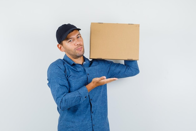 Giovane che tiene una scatola di cartone con palmo aperto in camicia blu, berretto e sembra felice. vista frontale.