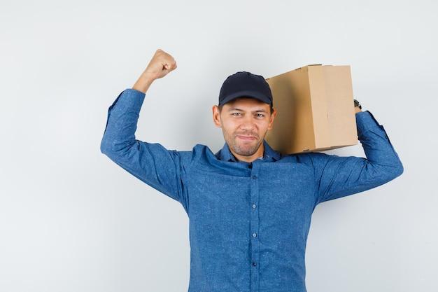 Молодой человек держит картонную коробку с жестом победителя в голубой рубашке, кепке и выглядит удачливым, вид спереди.